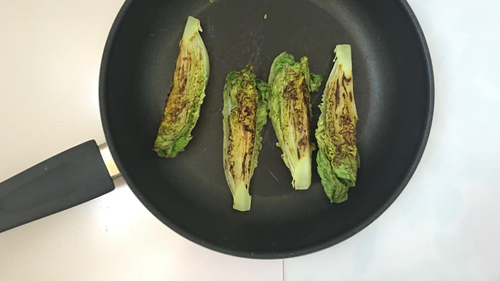 Delicious grilled romaine lettuce with grated parmesan cheese and olive oil, a surprising vegetable side dish for chicken or pork!
